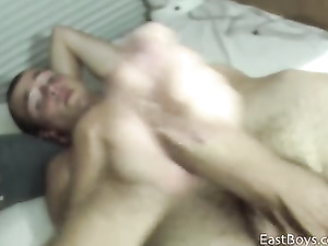 Bald twink is lying on the bed and pleasuring hot handjob