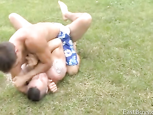 Sexy strong muscled wrestler are training on the grass