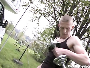 Strong young twink is lifting dumbbell at the park