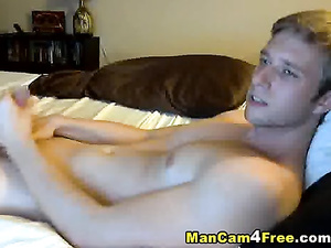 Beautiful blond twink is lying on the bed and hotly masturbating dick