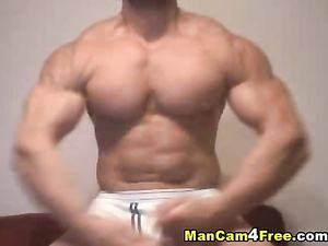 Bodybuilder excitingly poses in front of the camera nude